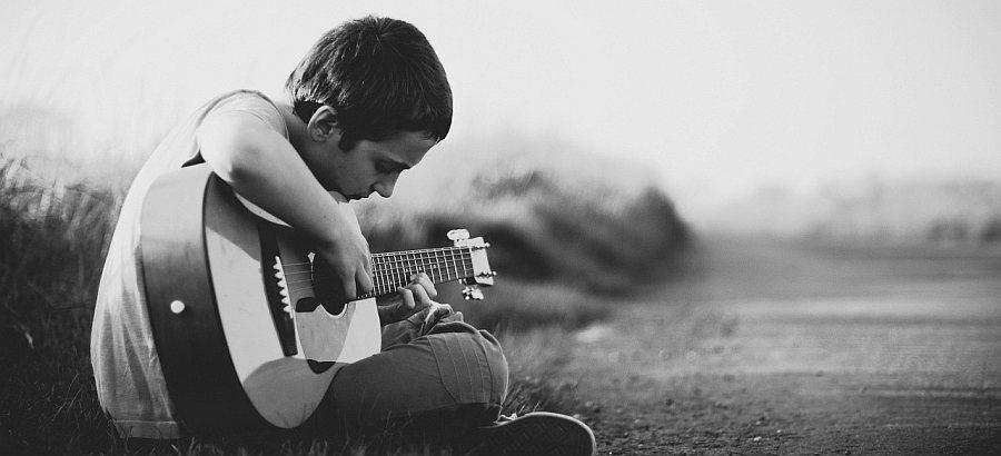 Junge mit Gitarre spielt Musik